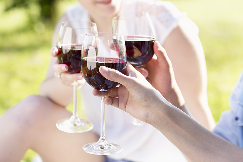3 hands, holding glasses of red wine, toasting, at a summer party outdoors